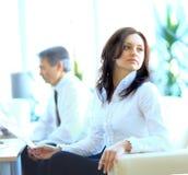 Femme réussie d'affaires s'asseyant avec son personnel à l'arrière-plan au bureau Images libres de droits