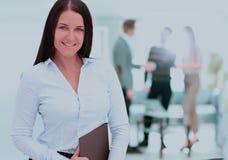 Femme réussie d'affaires se tenant avec son personnel à l'arrière-plan Image stock