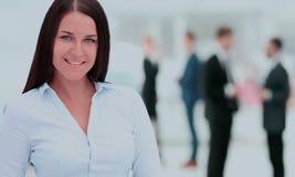 Femme réussie d'affaires se tenant avec son personnel à l'arrière-plan Photographie stock libre de droits