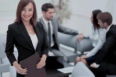 Femme réussie d'affaires se tenant avec son personnel à l'arrière-plan Photos stock