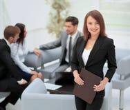 Femme réussie d'affaires se tenant avec son personnel à l'arrière-plan Photo stock