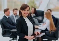 Femme réussie d'affaires se tenant avec son personnel à l'arrière-plan au bureau Photo stock