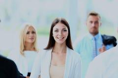 Femme réussie d'affaires se tenant avec son personnel à l'arrière-plan au bureau Photographie stock libre de droits