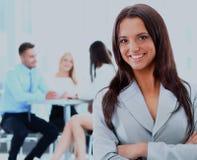 Femme réussie d'affaires se tenant avec son personnel à l'arrière-plan au bureau Images stock