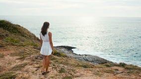 Femme rêvant au bord de la falaise au coucher du soleil sur le fond de l'océan clips vidéos