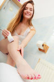 Femme rasant des jambes avec le depilator dans la salle de bains Images stock