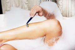Femme rasant sa jambe photographie stock