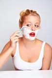 Femme rasant son visage Image stock