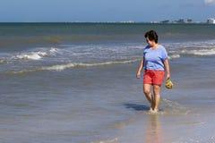 Femme rassemblant des coquilles dans le ressac dans le Golfe du Mexique Photo stock
