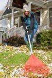 Femme ratissant des feuilles dans la cour dans la chute image libre de droits