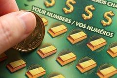 Femme rayant des billets de loterie Photo stock