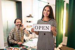 Femme rayonnante de attirance de sourire heureuse tenant un signe ouvert photographie stock libre de droits
