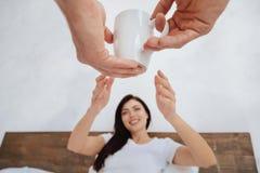 Femme rayonnante prenant la tasse de café de l'homme Image stock