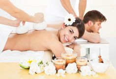 Femme recevant le massage avec les timbres de fines herbes de compresse Photographie stock