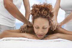 Femme recevant le massage d'épaule des esthéticiens photo stock