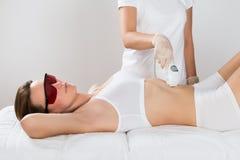Femme recevant le traitement de laser d'Epilation sur le ventre image stock