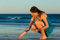 Femmes recherchant des coquilles au coucher du soleil Photos libres de droits