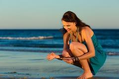 Femmes recherchant des coquilles au coucher du soleil Images libres de droits