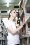 Femme recherchant des livres dans la bibliothèque Images libres de droits