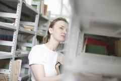 Femme recherchant des livres dans la bibliothèque Photos libres de droits