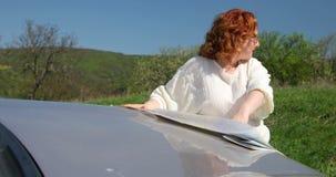Femme recherchant la bonne direction utilisant la carte de papier sur le capot banque de vidéos