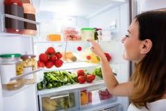 Femme recherchant la nourriture dans le réfrigérateur images libres de droits