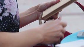 Femme recherchant quelque chose dans la bourse, désordre dans le sac, pickpocketing, accessoires banque de vidéos