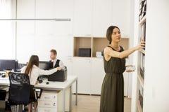 Femme recherchant quelque chose dans le bureau Photographie stock libre de droits