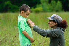Femme rectifiant l'enfant Photographie stock