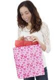 Femme regardant à son sac de cadeau Images stock