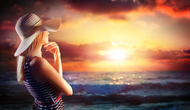 Femme regardant dans le coucher du soleil sur la mer Photo libre de droits