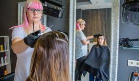 Femme regardant dans le miroir à la peignée de coiffeur Photographie stock libre de droits