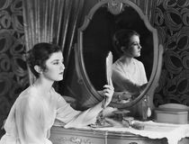Femme regardant dans le miroir (toutes les personnes représentées ne sont pas plus long vivantes et aucun domaine n'existe Garant Photos libres de droits