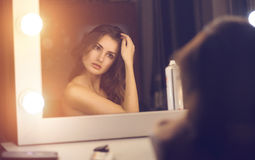 Femme regardant dans un miroir Photo stock