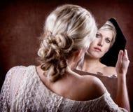 Femme regardant dans un miroir cassé Photos stock