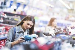 Femme regardant des chaussures dans le magasin Photo stock