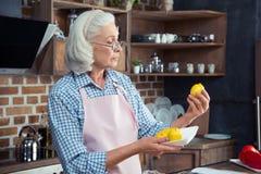 Femme regardant des citrons dans la cuisine Photos stock