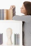 Femme regardant des livres sur l'étagère Images libres de droits