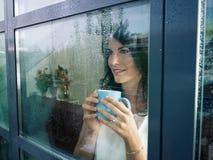 Femme regardant fixement l'hublot Photographie stock