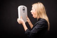 Femme regardant l'échelle de poids dans le choc image stock