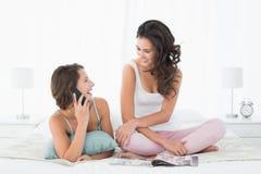 Femme regardant l'ami féminin gai à l'appel dans le lit Photo libre de droits