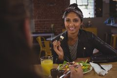 Femme regardant l'ami tout en ayant la salade en café Images stock