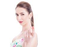Femme regardant l'appareil-photo faisant le geste attrayant avec l'index fing Image libre de droits