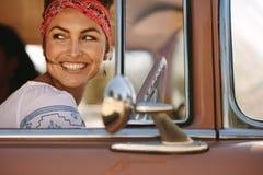 Femme regardant l'extérieur tout en conduisant photographie stock