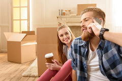 Femme regardant l'homme barbu parlant sur le smartphone se reposant sur le plancher dans la nouvelle maison Images libres de droits