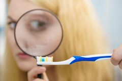 Femme regardant la brosse à dents par la loupe image libre de droits