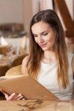 Femme regardant la carte de menu Photographie stock