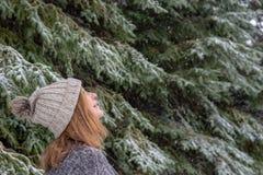 Femme regardant la chute de neige photographie stock libre de droits