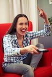 Femme regardant la TV et montrant le signe de roche Photos stock