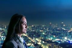 Femme regardant la ville de nuit Photos stock